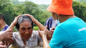 A person coming out of the water at theThai Baptism