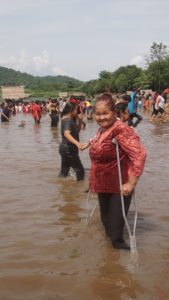 Woman on crutches at Thai Baptism
