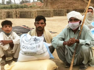 3 Generations of kiln workers from Pakistan getting food from VKP